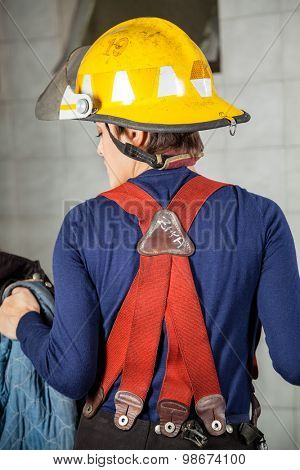 Rear view of firewoman in uniform standing at fire station