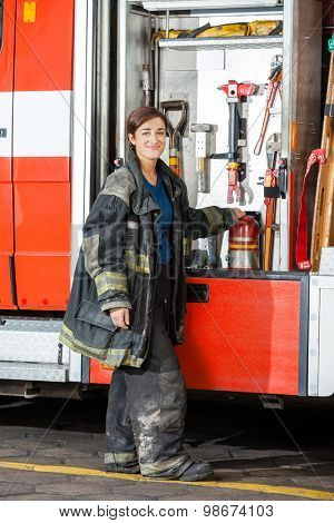 Full length portrait of smiling female firefighter standing by truck at fire station