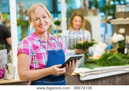 Portrait of smiling mature female florist holding digital tablet with colleague working in background at shop