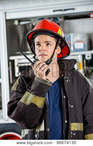 Confident young firefighter looking away while using walkie talkie at fire station