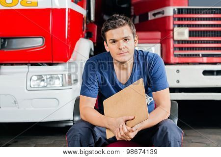 Portrait of confident male firefighter holding clipboard while sitting against firetrucks at station