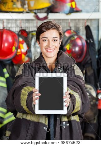 Portrait of happy firewoman showing digital tablet at fire station