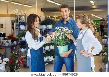Portrait of male customer being assisted by salesgirls in buying flower plants at store
