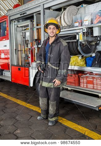 Full length portrait of confident fireman holding coffee mug while standing by truck at fire station