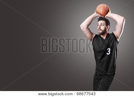 Basketball Player on a black uniform on gray background