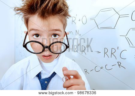Funny schoolboy in big glasses standing by the school board. Chemistry. Science and education.