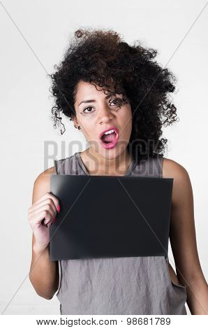 Hispanic brunette model with afro like hair wearing grey sleeveless shirt holding up blank board as