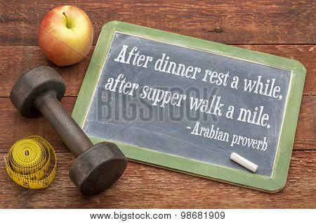 After dinner rest a while, after supper walk a mile -  Arabic proverb on a slate blackboard sign against weathered red painted barn wood with dumbbell, apple and tape measure - healthy living concept