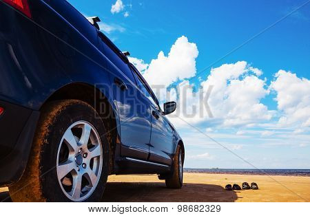 Car Standing On A Sandy Beach And Two Pairs Of Beach Slippers