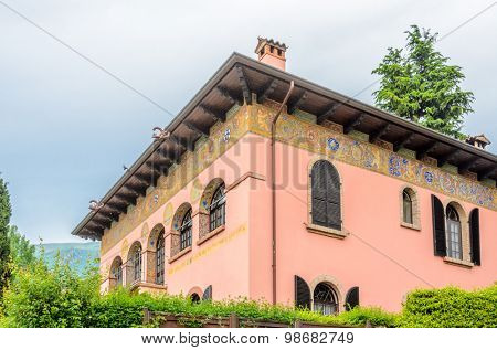 Fragment of a beautiful building with windows decorated with flowers in Italy