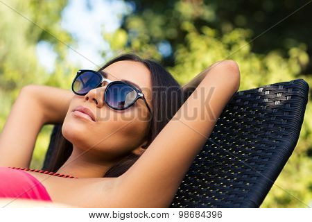 Portrait of a lovely woman sunbathing on the deckchair outdoors