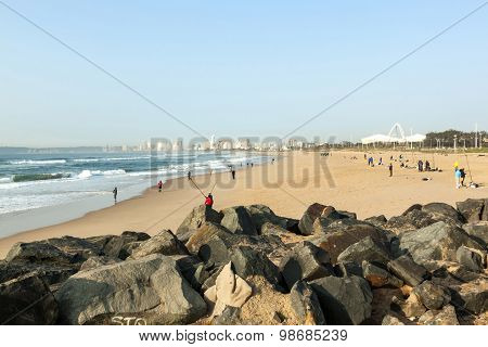 Fishermen On  Beach With Stadium And Skyline In Background