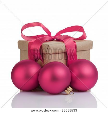 wraped gift box with purple bow, christmas balls and tag, isolated