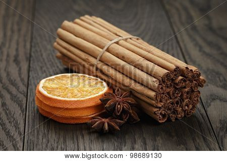true cinnamon sticks and dried oranges, oak table