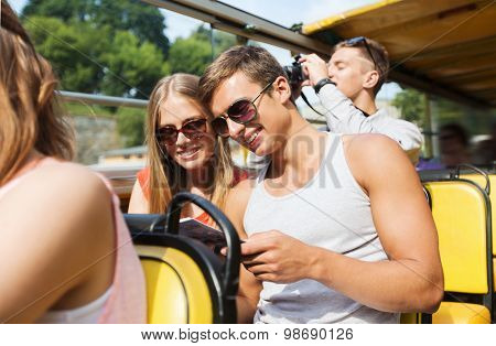 friendship, travel, vacation, summer and people concept - smiling couple in sunglasses with guidebook traveling by tour bus