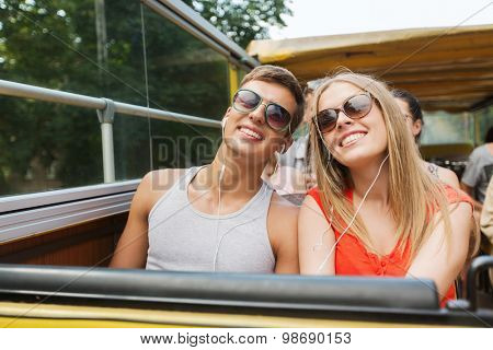 travel, tourism, summer vacation, sightseeing and people concept - happy teenage couple in sunglasses traveling by tour bus and listening to music with earphones