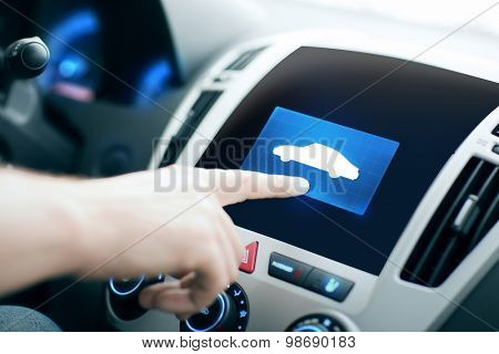 transport, modern technology and people concept - male hand pointing finger to car icon on control panel screen