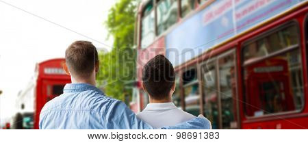 people, homosexuality, same-sex marriage, travel and love concept - close up of happy male gay couple hugging from back over london city street background