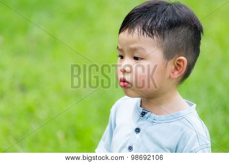 Little boy look at other side with funny face