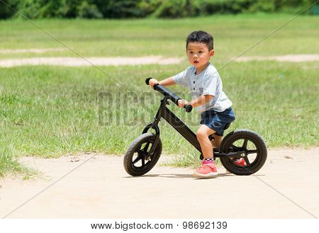 Baby boy riding with balance bicycle