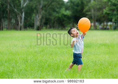 Small kid play with orange balloon