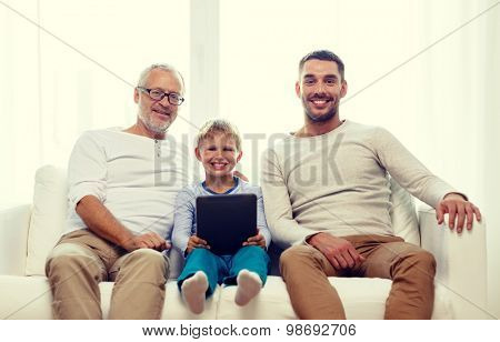 family, generation, technology and people concept - smiling father, son and grandfather sitting on couch with tablet pc computer at home