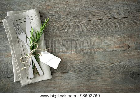 Silverware with a twige of rosemary and empty tag on rustic wooden background