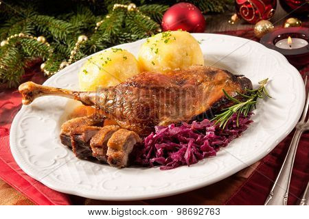 Crusty goose leg with braised red cabbage and dumplings on Christmas decorated table