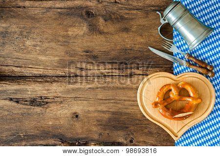 Oktoberfest festival background with beer mug, pretzel on cutting board and cutlery set