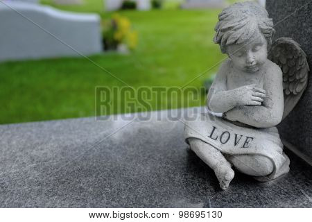Antique marble statue of a Cherub angel with word love carved into stone