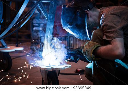 Employee welding using MIG/MAG welder.