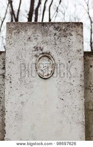 Old Gravestone With Damaged Portrait Of The Buried Person