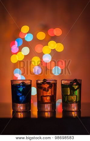 Three shots glasses full of assorted beverages and ice on golden blurred lighting bokeh background