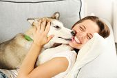 Woman lying with her malamute dog on sofa in room poster