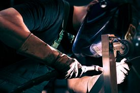 stock photo of tig  - Employee welding steel using TIG welder machine - JPG