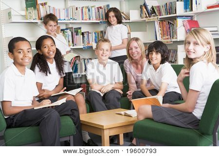 Seven students in library reading books with teacher