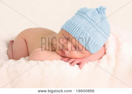 Newborn baby boy in a blue knitted hat.