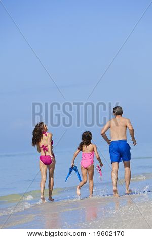 Rear view of a happy family of mother, father and child, a daughter, running holding hands and having fun in the waves of a sunny beach