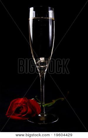 An engagement ring inside a glass of champagne
