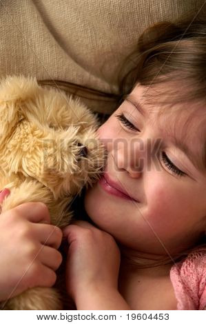 A young girl looking at her teddy bear