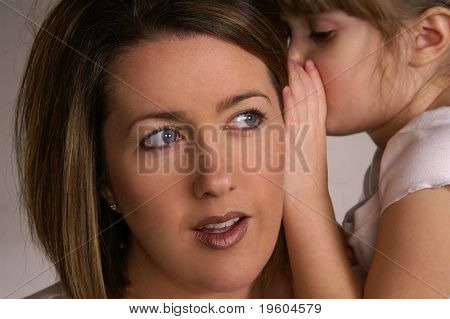 A young girl whispering secrets in her mommy's ear