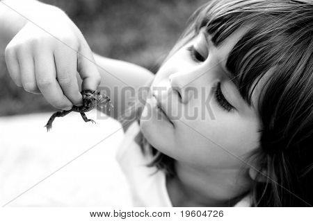 A cute girl holding a toad with shallow depth of field with focus on toad