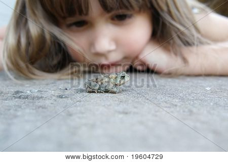 A cute young girl watching a toad on the ground, shallow depth of field with focus on toad