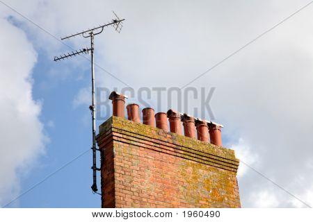 Old British Chimneystack And An Analogue Tv Aerial.