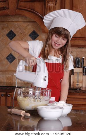 A cute young girl mixing cake mix for cupcakes