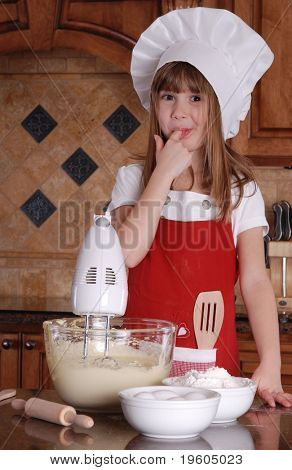 A cute young girl tasting the cake batter