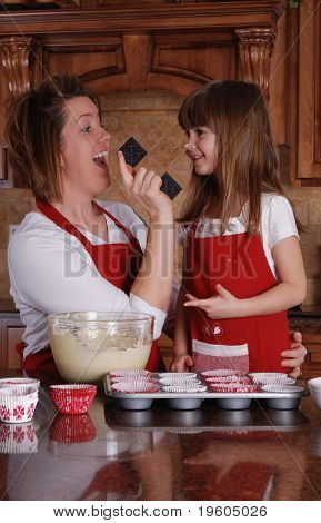 A cute young girl and her mother having fun while baking cupcakes