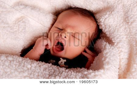 A portrait of a cute baby yawning