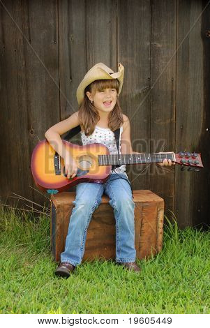 A cute young girl playing the guitar