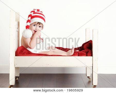 A cute baby boy eating a candy cane in a little bed